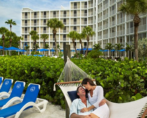 A couple in a poolside hammock near chaise lounge chairs.