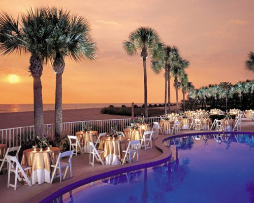 Evening poolside dining with beach view.