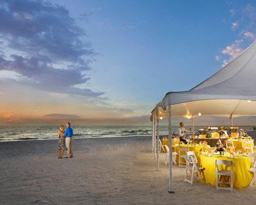 Outdoor buffet on the beach at dusk.