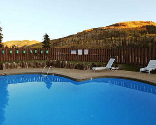 An outdoor swimming pool with mountain view.
