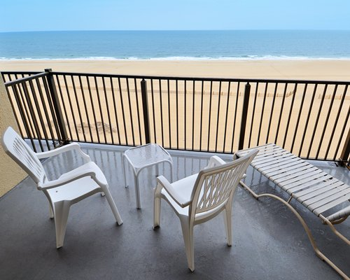 Balcony with patio furniture overlooking a beach.