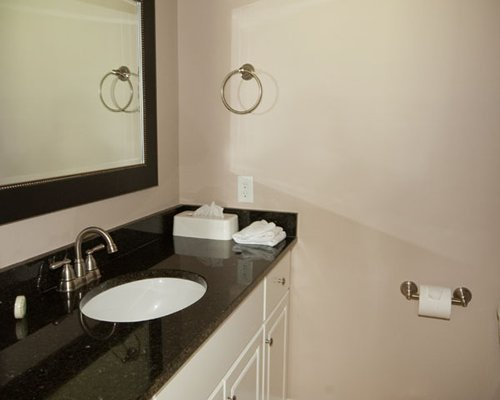 A bathroom with a counter top wash basin and a large mirror.