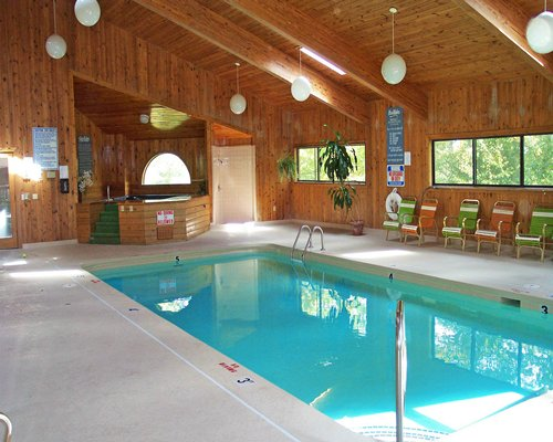 A wooden cabin with indoor pool and hot tub.