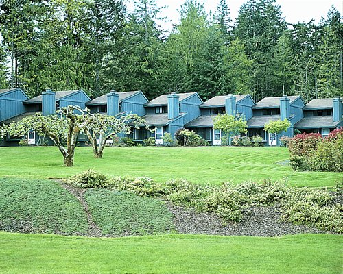 View of multiple vacation units surrounded by lawns and trees.