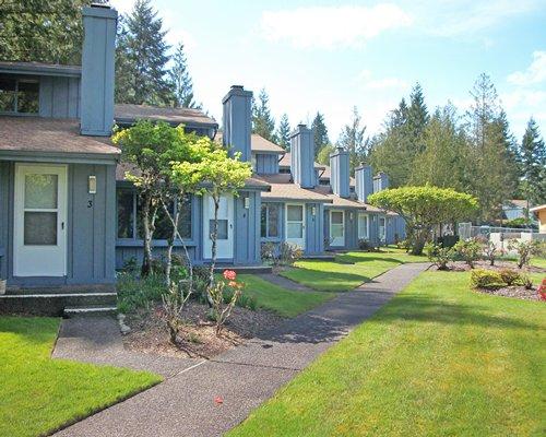 Multiple units of Blue Heron Resort alongside lawn near wooded area.