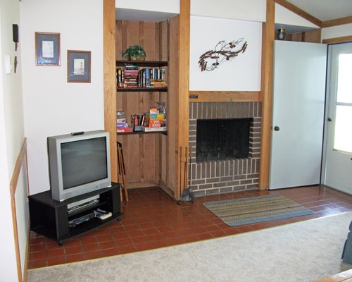 A living room with a television and a fireplace.