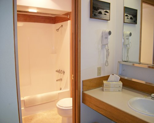 A bathroom with open vanity and enclosed toilet and bathing area.