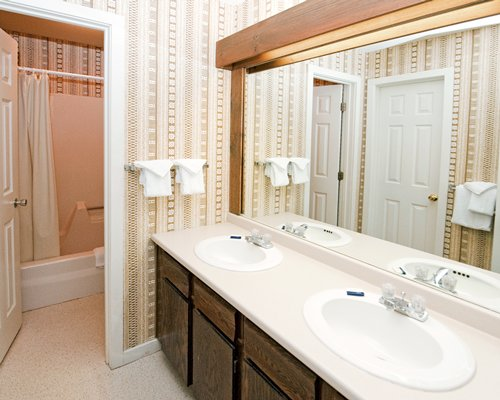 A bathroom with counter top wash basin and mirror.