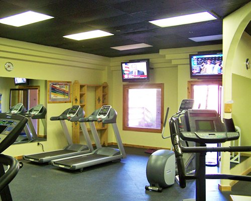 A well equipped fitness center with televisions.