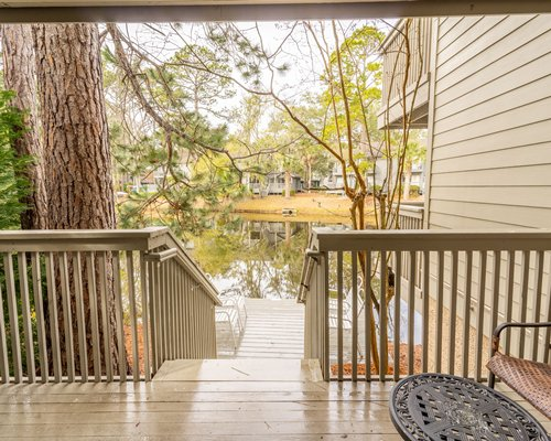 Waterside deck with furniture and view of multi-story units amongst trees.