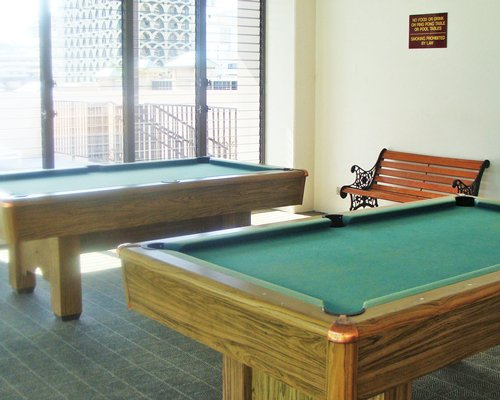 A view of two pool tables in a recreational room.