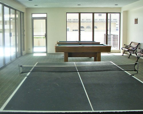 An indoor recreation room with pool tables and table tennis.