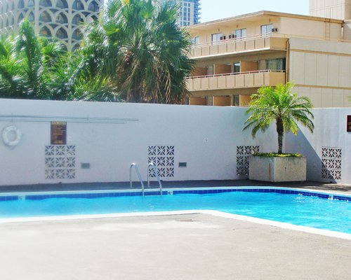 An outdoor swimming pool alongside multi-story condos.