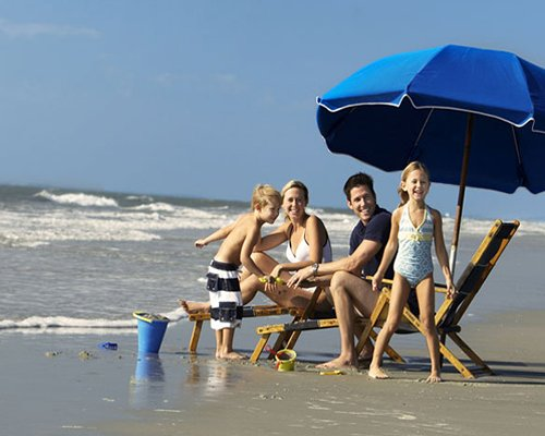 A family at the beach with chaise lounge chairs and sunshade.