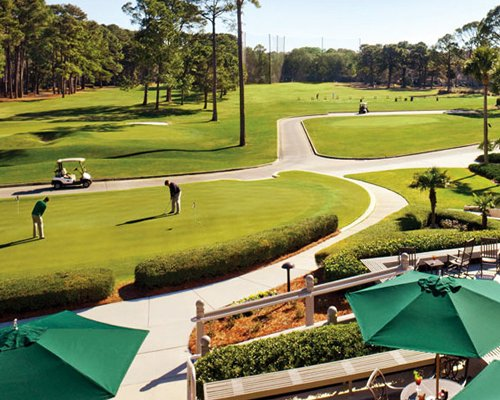 Exterior view of the golf course with sunshades and patio furniture.