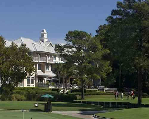 Scenic exterior view of Sea Pines Plantation with golf course and sunshades.