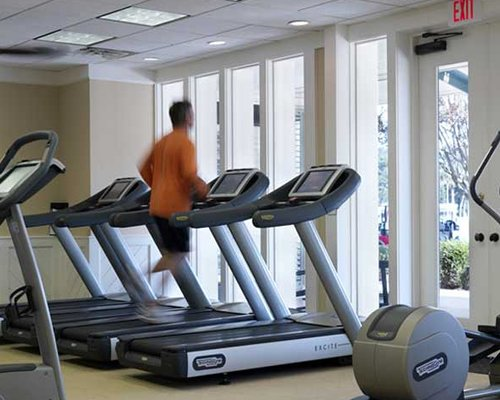 A well equipped fitness center with a man at the treadmill.