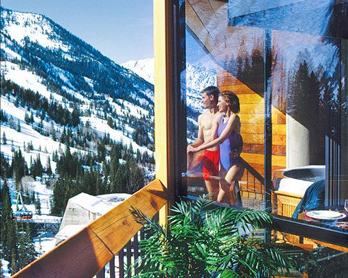 A couple looking at a snowy mountain from a balcony.