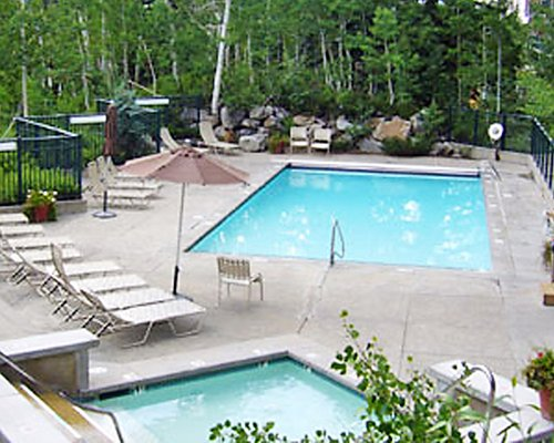 An outdoor swimming pool and hot tub with chaise lounge chairs surrounded by wooded area.