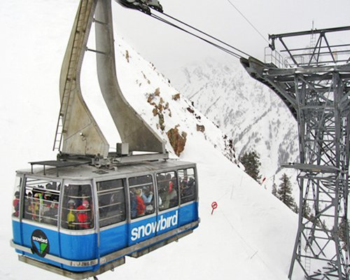 Cable car surrounded by a snowy mountain.