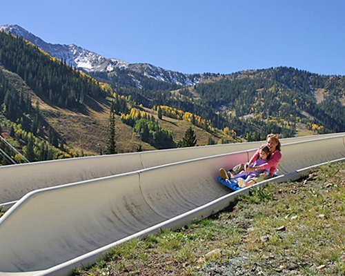 A woman and a kid enjoying an alpine slide alongside mountains.