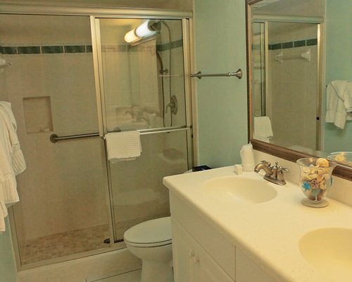 A bathroom with shower and two sinks accompanied with a vanity.