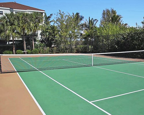 An outdoor tennis court alongside resort suites.