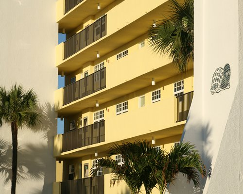 A street view of a multi-story resort unit alongside palm trees.