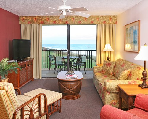 Furnished living room with a television and patio furniture on balcony alongside ocean.