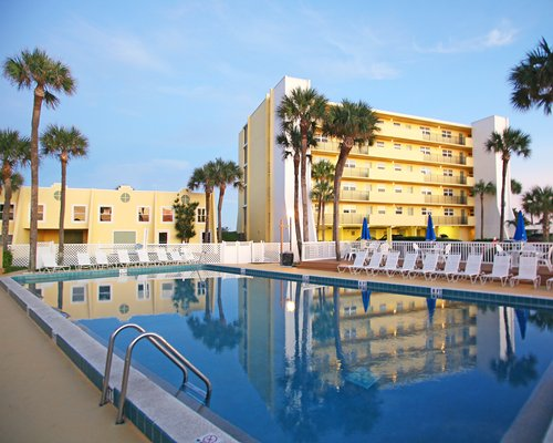 Exterior view of multiple unit balconies with outdoor swimming pool and palm trees.