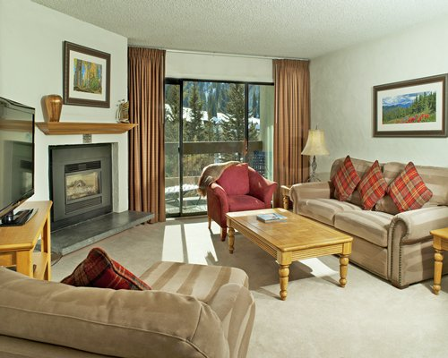 A well furnished living room with pullout sofa, television, balcony, and a fire place.