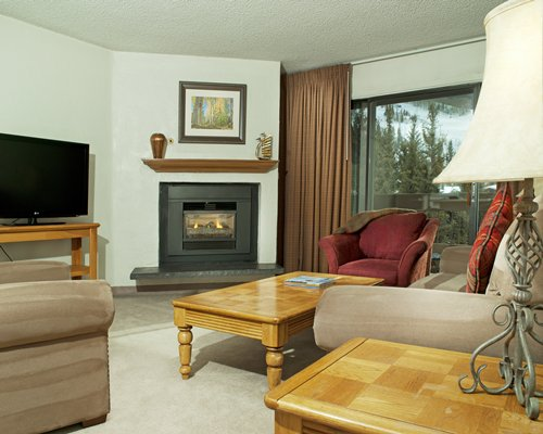 A well furnished living room with television, fireplace, and an outside view.