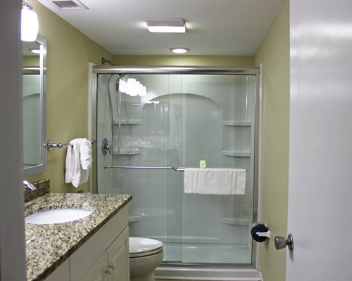 A bathroom with a stand-up shower, sink, toilet, and vanity.