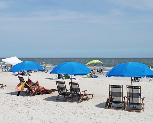 View of ocean from the beach with chaise lounge chairs and sunshades.