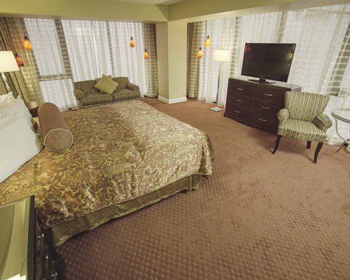 A well furnished bedroom with king bed, television, and outdoor view.