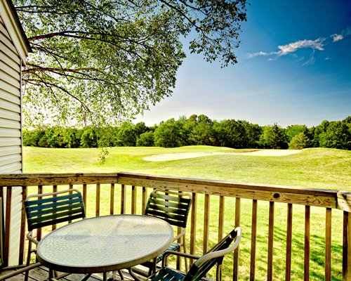 Balcony with patio table with a view of golf course.