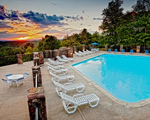 An outdoor swimming pool with chaise lounge chairs at dusk.