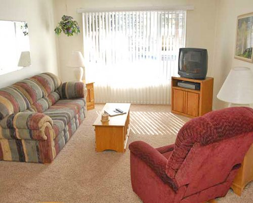 Living room with a television and two sofas.