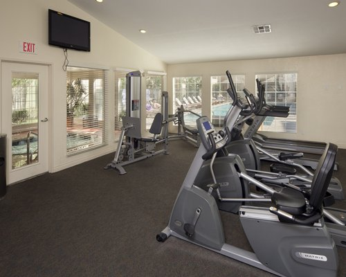 A well equipped fitness center with television.