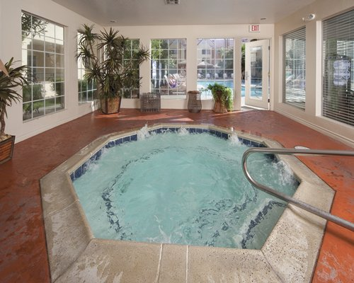 An indoor swimming pool with hottub and chaise lounge chairs.