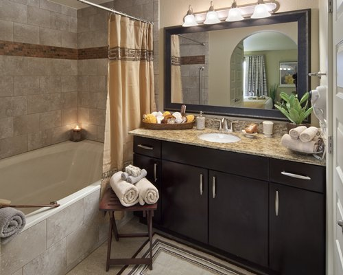 A bathroom with single sink vanity and a bathtub.