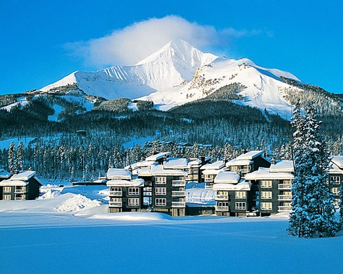 Scenic view of Lake Condominiums resort at the foothills of a snowy mountain.