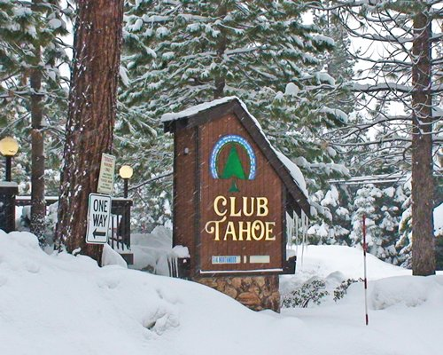 A signboard and entry gate of the Club Tahoe resort covered in snow.