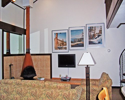 Furnished living room with fireplace television stairway and indoor balcony.