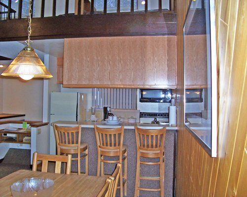 A well furnished dining alongside a kitchen with a breakfast bar.