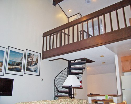 A well furnished living room with television spiral stairway and open second story.