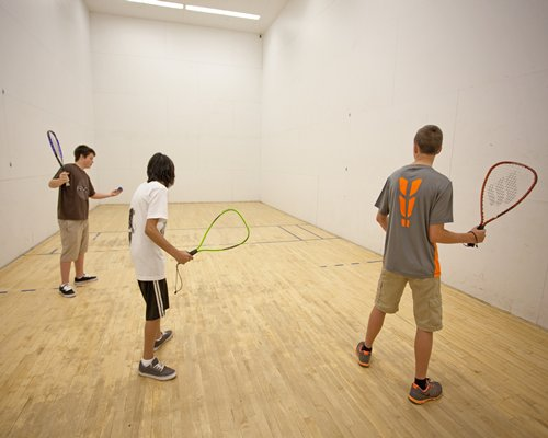 Indoor racquetball court with people playing racquetball.