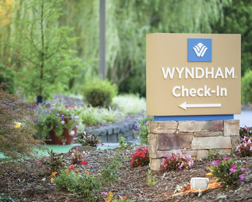 A signboard of Wyndham Resort surrounded by shrubs and trees.