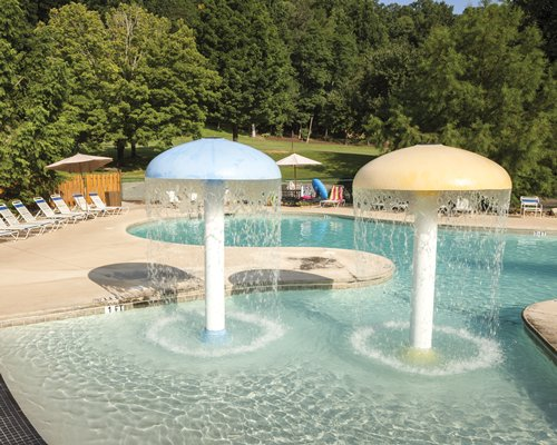 An outdoor swimming pool with two raining mushroom umbrellas alongside chaise lounge chairs and a wooded area.