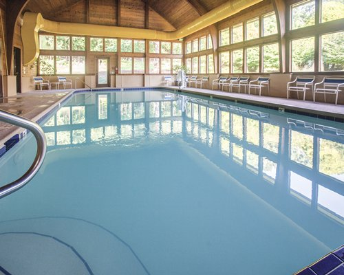 A glass covered indoor swimming pool with patio chairs.